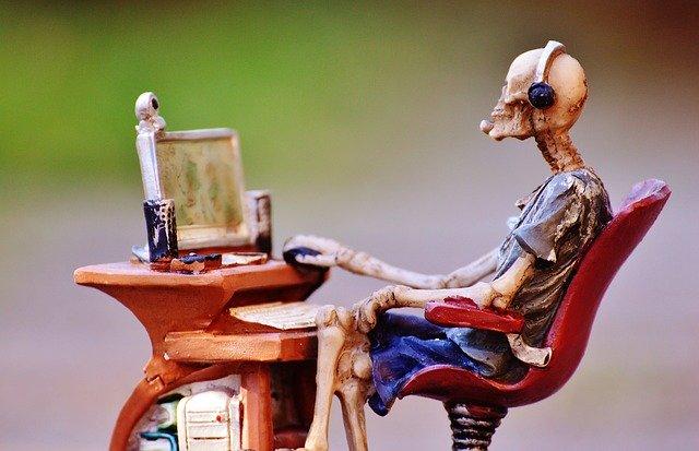 Skelet med tøj på sidder foran computer og udfylder noget - det kunne være tilgængelighedserklæringen